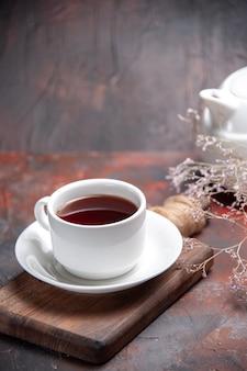 Front view cup of tea on dark table  dark biscuit