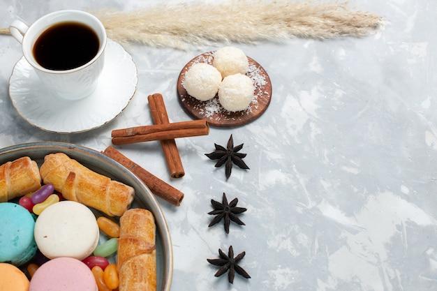 Vista frontale tazza di tè con bagel e macarons su bianco