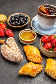 Vista frontale tazza di tè con biscotti e frutta sulla torta dolce di frutta superficie scura