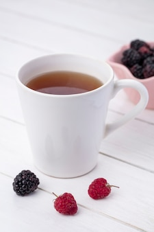 Front view of cup of tea with blackberries and raspberries on a white surface