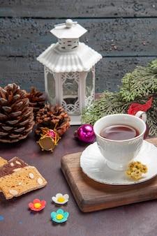 Vista frontale tazza di tè con fette di torta su uno spazio buio