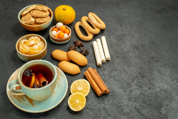 Front view cup of tea with candies biscuits and fruits on grey table tea sweet cookie