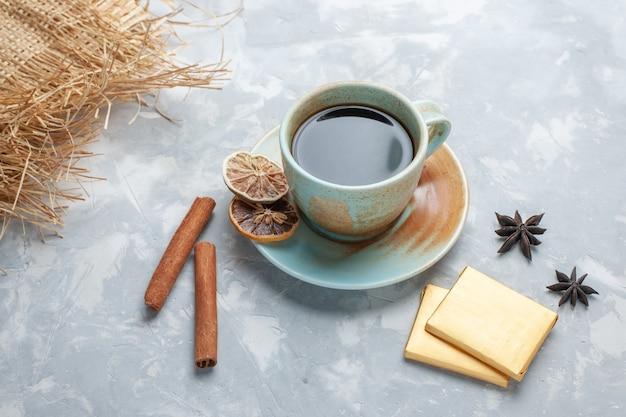 Vista frontale tazza di tè con caramelle e cannella sulla colazione colore caramella tè scrivania bianca