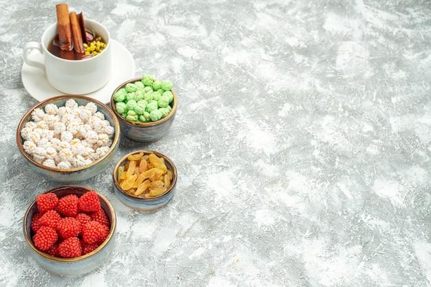 Vista frontale tazza di tè con caramelle e confetture su spazio bianco