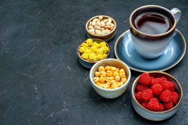 Tazza di tè di vista frontale con le caramelle sul biscotto dolce del tè dello zucchero candito di superficie grigia