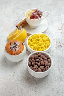 Vista frontale tazza di tè con caramelle e fette di limone su spazio bianco