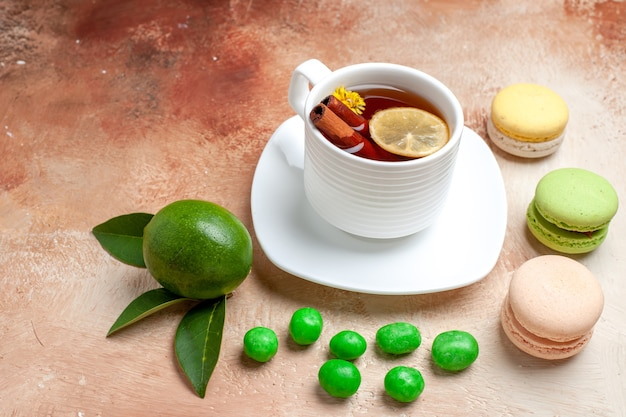 Front view cup of tea with candies and macarons on light brown table tea lemon biscuit