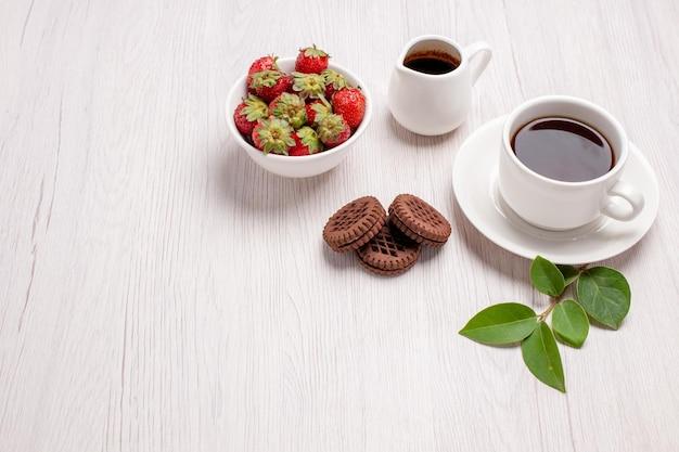 Vista frontale tazza di tè con biscotti al cioccolato e fragole su scrivania bianca zucchero tè biscotti dolce biscotto