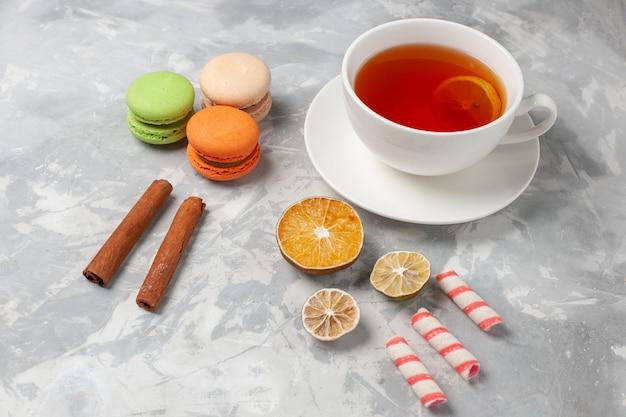 Vista frontale tazza di tè con cannella e macarons francesi sulla scrivania bianca