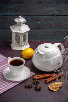 Vista frontale tazza di tè con cannella e bollitore sulla superficie scura bevanda per il tè di colore limone