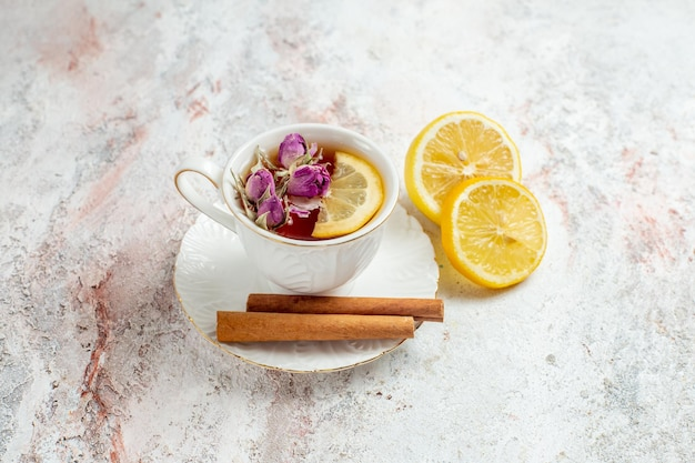 Vista frontale tazza di tè con cannella e fette di limone su uno spazio bianco chiaro