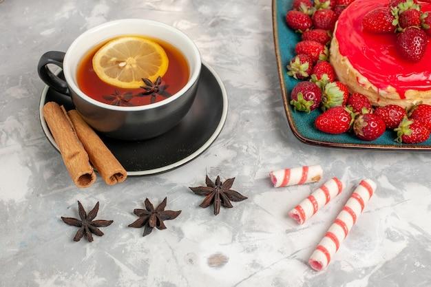 Vista frontale tazza di tè con cannella e piccola torta di fragole su superficie bianca
