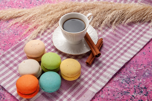 Vista frontale tazza di tè con cannella e macarons su rosa scrivania torta biscotto zucchero dolce