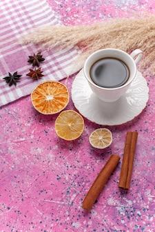 Tazza di tè con cannella sul rosa vista frontale