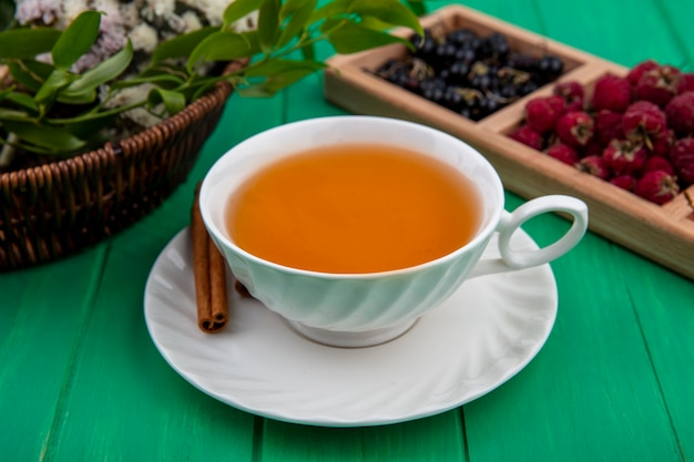 Front view of cup of tea with cinnamon raspberries and black currants on a green surface