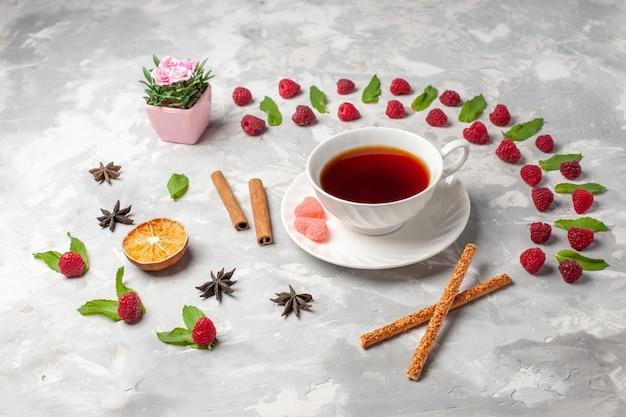 Tazza di vista frontale di tè con cannella sulla cannella della frutta della bacca del tè di superficie bianca