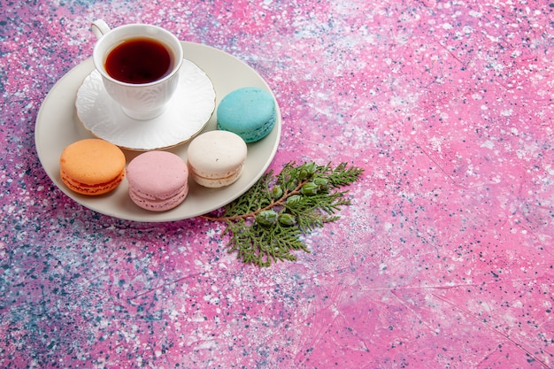 Front view cup of tea with colorful french macarons on pink surface