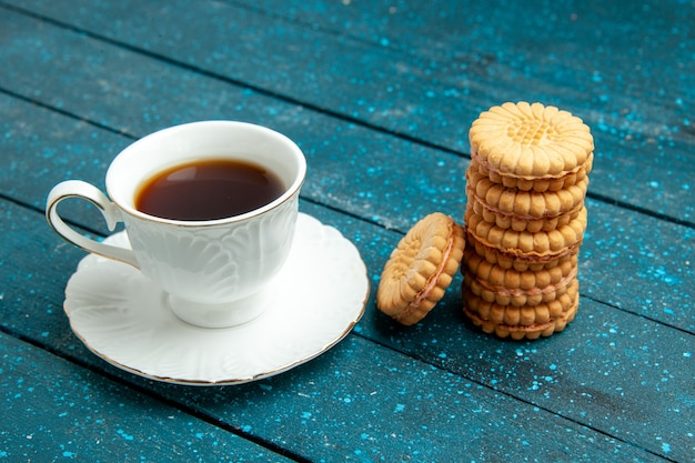 Front view cup of tea with cookies on blue rustic desk tea sugar biscuit cookie