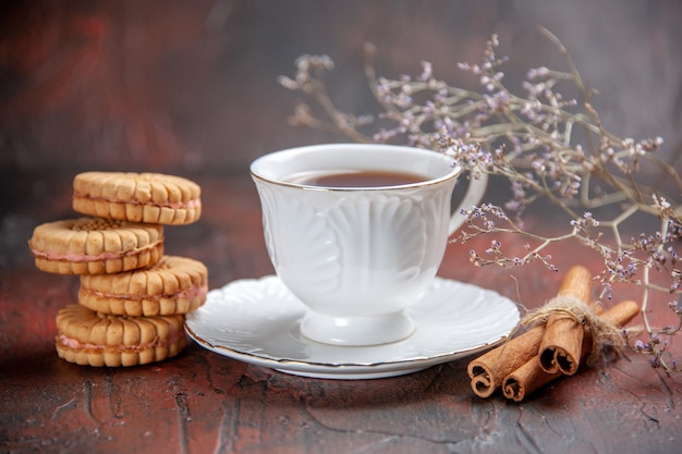 Front view cup of tea with cookies on dark background
