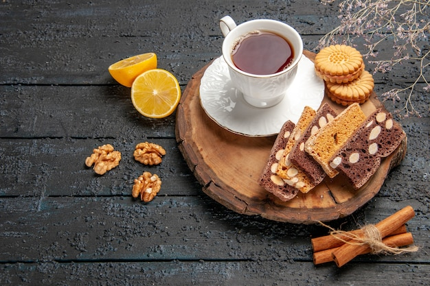Front view cup of tea with cookies and fruits on the dark desk ceremony sweet biscuits sugar