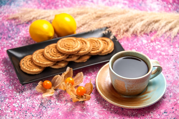 Front view cup of tea with cookies and lemon on pink desk.