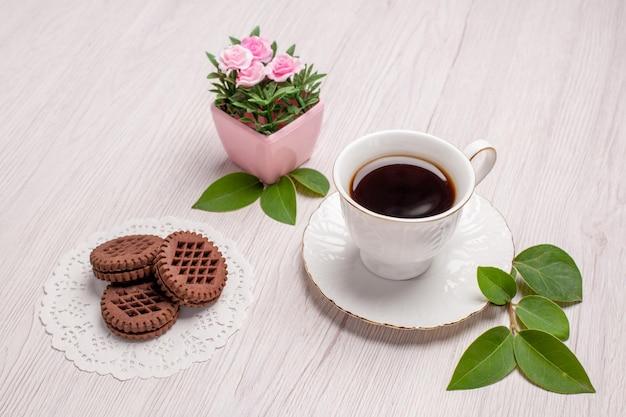 Tazza di tè con i biscotti di vista frontale sul biscotto dolce del biscotto del tè dello zucchero da tavola bianco
