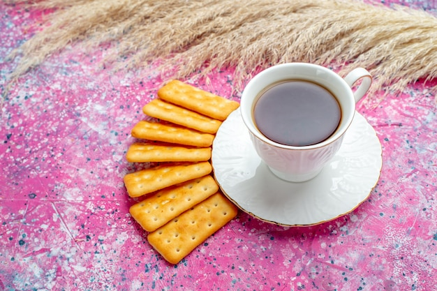 Front view cup of tea with crackers on pink desk