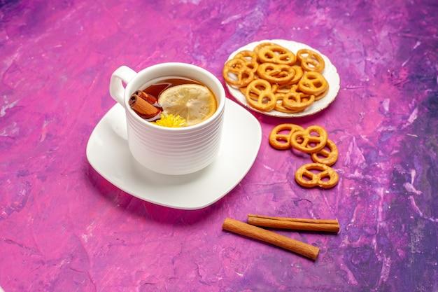 Vista frontale tazza di tè con cracker sul tavolo rosa color caramella al limone tè
