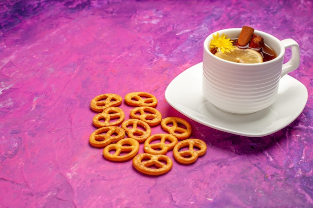 Vista frontale tazza di tè con cracker su un tavolo rosa tè color caramella al limone