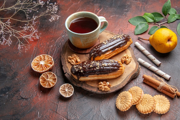 Front view cup of tea with delicious choco eclairs on dark background
