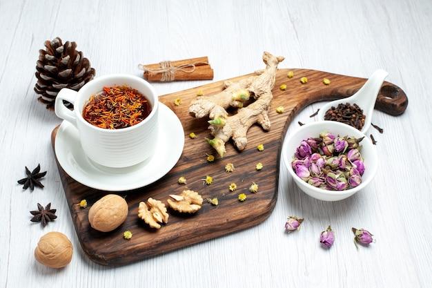 Vista frontale tazza di tè con fiori secchi e noci su sfondo bianco tè bevanda dado