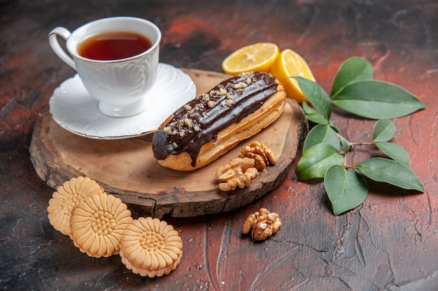 Front view cup of tea with eclair and cookies on dark background