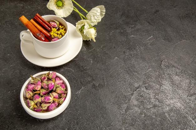 Vista frontale tazza di tè con fiori e cannella su spazio grigio