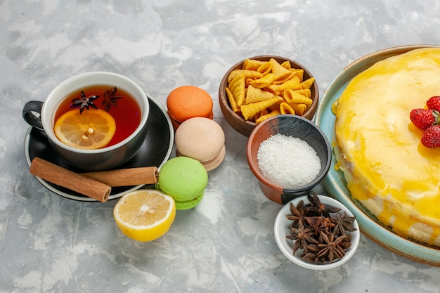 Vista frontale tazza di tè con macarons francesi e deliziosa torta sciroppo giallo su superficie bianca