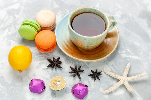 Front view cup of tea with french macarons and lemon on light desk cake bake bisciut pie sweet sugar