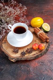 Vista frontale tazza di tè con limone e cannella su sfondo scuro