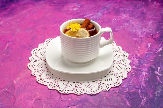 Vista frontale tazza di tè con limone e cannella su caramelle color tè da tavola rosa
