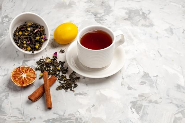 Vista frontale tazza di tè con limone e cannella su uno spazio bianco