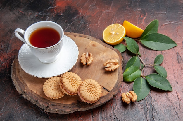 Front view cup of tea with lemon and cookies on a dark background