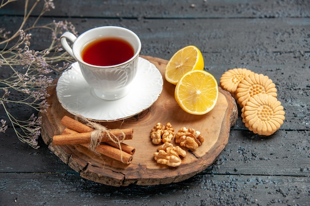 Front view cup of tea with lemon and cookies on dark background