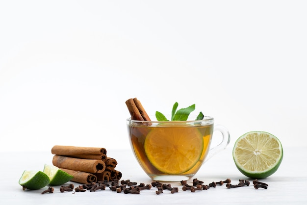 A front view cup of tea with lemon mint and cinnamon on white, tea dessert candy