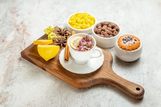 Vista frontale tazza di tè con fette di limone e caramelle su spazio bianco