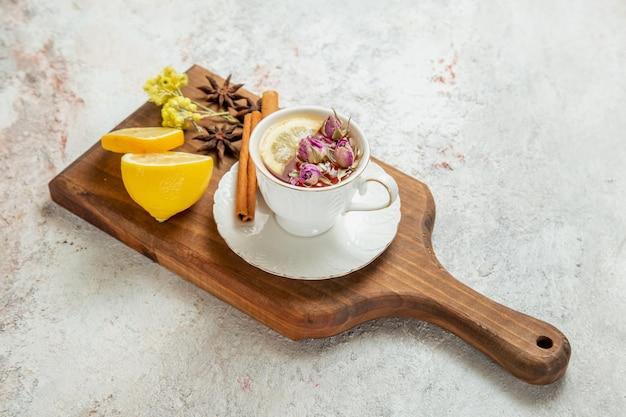 Vista frontale tazza di tè con fette di limone su uno spazio bianco