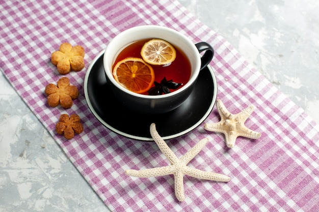 Vista frontale tazza di tè con fette di limone su una superficie bianca