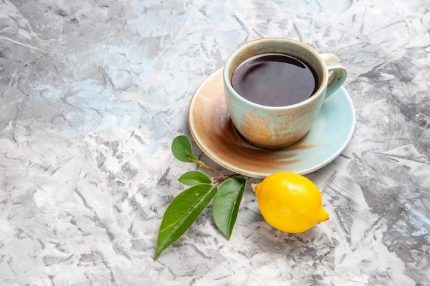 Vista frontale tazza di tè con limone sulla bevanda di tè alla frutta da tavola bianca