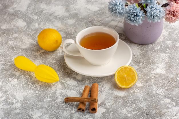Vista frontale tazza di tè con limoni e cannella sullo scrittorio bianco chiaro