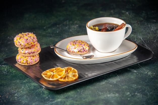 Vista frontale tazza di tè con piccoli biscotti dolci nel piatto e vassoio sulla superficie scura cerimonia di vetro dolce colazione torta dessert colore