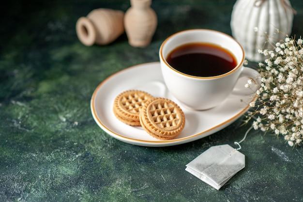Vista frontale tazza di tè con piccoli biscotti dolci nel piatto bianco sulla superficie scura colore cerimonia colazione pane vetro bevanda zucchero