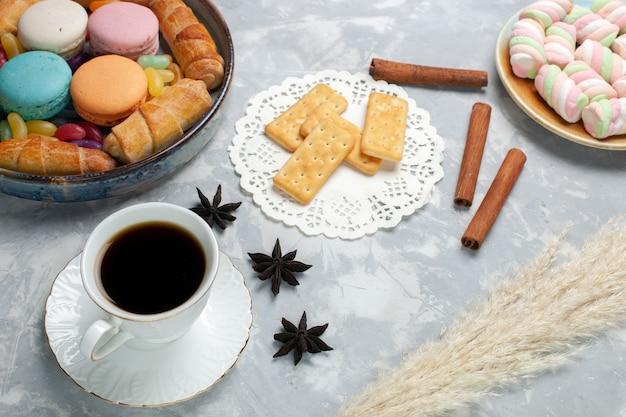 Vista frontale tazza di tè con macarons e bagel su bianco