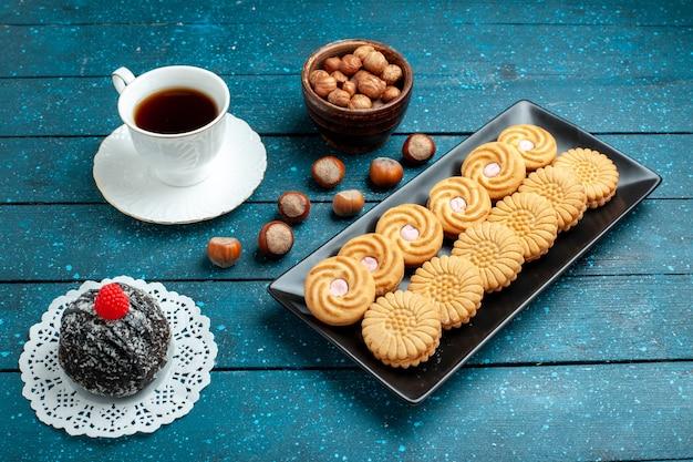 Vista frontale tazza di tè con noci e biscotti sulla torta di biscotto dolce del biscotto dello zucchero dello scrittorio blu rustico